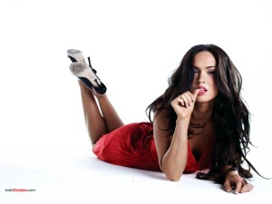 Megan Fox posing lied down with a red dress