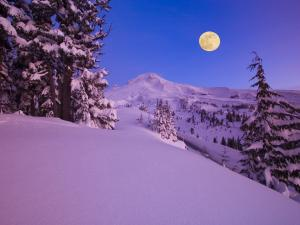 Full moon over snowy mountains