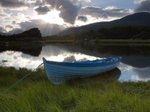 Boat on the shore of a small lake at sunset