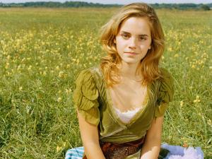Emma Watson sitting on a meadow