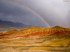Rainbow merging with the mountain
