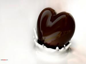 Heart of black chocolate dipping in milk