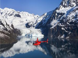 Small red helicopter flying over a lake between snow mountains