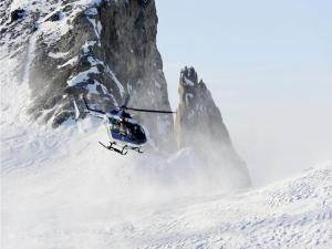 Helicopter between snowy mountains