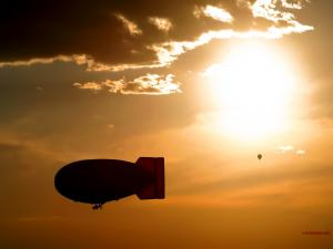 Airship and balloon under a golden sky
