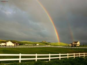 Rainbow decorating a landscape of farms