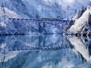 Train crossing a bridge in a winter landscape