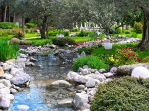 Garden with a small river, plants and colorful flowers