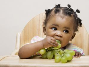 Small girl eating white grapes