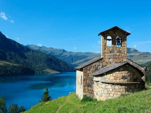 Stone chapel beside a blue lake