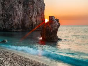 The Sun between two rocks, in a beach in Milos island (Greece)