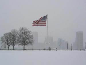 United States flag waving in a snowy landscape