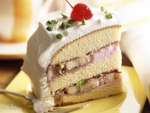 Piece of cake with cream, pistachios and a sour cherry