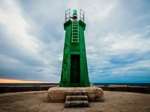 A green lighthouse in the harbour of Denia, Spain