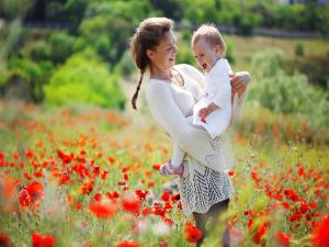 Mother walking with her ​​baby across a field of poppies
