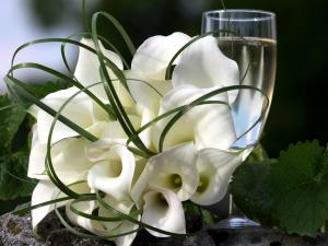 A bouquet of white calla lilies and a glass of wine