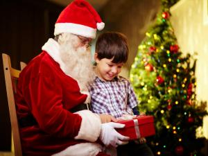 Santa Claus giving to a child his Christmas gift