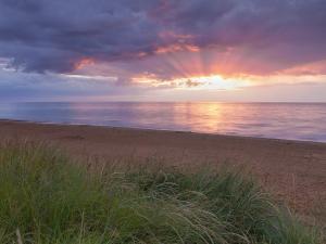The sun under clouds on a beach in Hunstanton, on the Norfolk coast, England