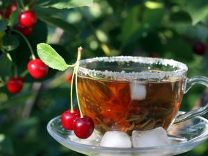 A cup of iced tea with two cherries