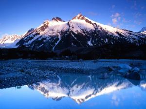 Mountain range reflected in blue water