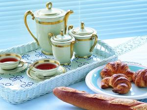 Breakfast with tea, bread and croissants