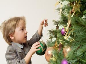 A boy decorating the Christmas tree