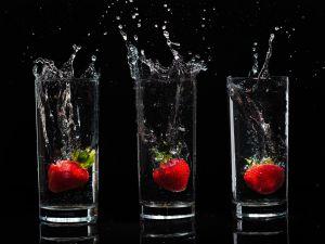 Strawberries inside of water vases