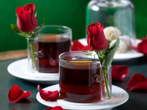 Two cups of tea with a rose