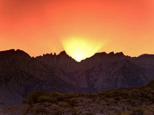 The sun illuminating an orange sky, in Alabama Hills (California)