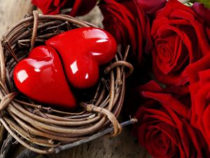 Two hearts in a basket, beside a some red roses