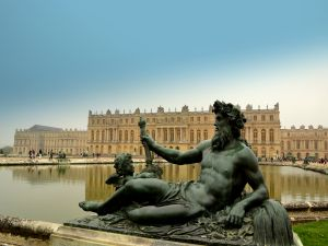 Statue with the Palace of Versailles at background (France)