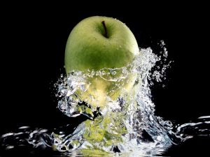 Green apple falling into water