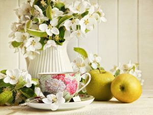 Cup of tea, accompanied by jasmine flowers and green apples