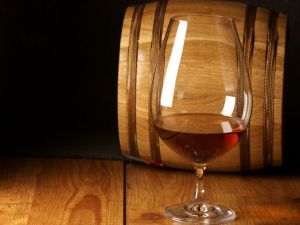 A cup with cognac beside a wooden barrel
