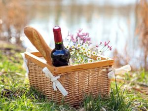 Basket with bread, red wine and flowers