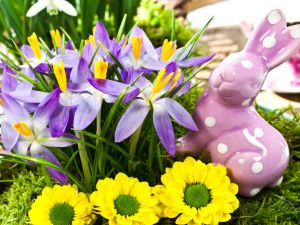 Figurine of a rabbit beside lilac and yellow flowers