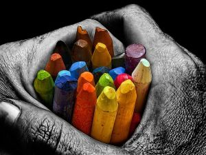 Hands holding a handful of colored waxes