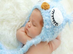 Baby sleeping with a blue cap
