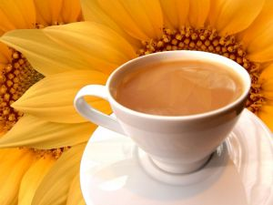 Coffee with milk and sunflowers in background
