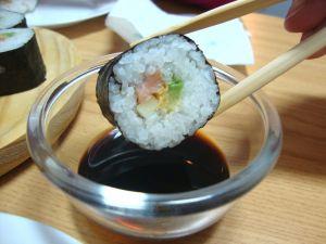 Wetting a nori maki in soy sauce