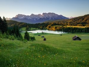 Cabins in a meadows at the foot of the Alps