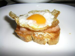 Slice of bread with meat and a quail egg