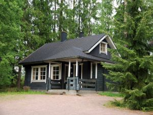 Black wooden house surrounded by pines