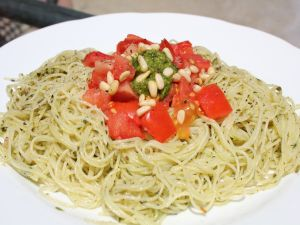 Spaghetti with pesto sauce, pine nuts and diced tomato