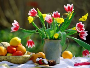 Table with tulips, fruits and a piece of cake