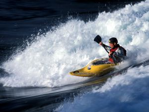 Taking a wave in kayak