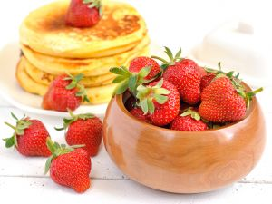 Wooden bowl with strawberries and pancakes