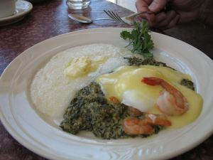 Poached eggs, creamy spinach and shrimps with hollandaise sauce and grits