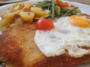 Breaded beef steak with egg and vegetables