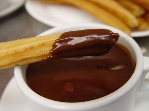 Wetting a churro in chocolate